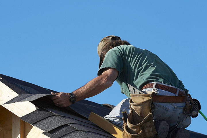 Gerry barja on the roof of home fixing shingles. Gerald barja